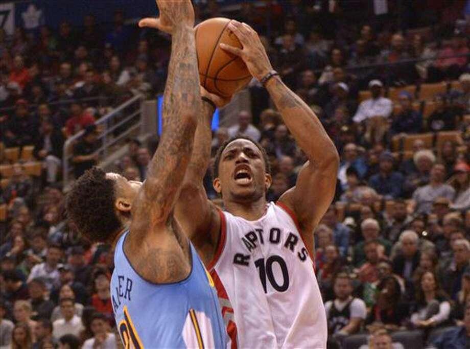 Toronto Raptors' DeMar DeRozan, right, shoots past Denver Nuggets' Wilson Chandler during the first half of their NBA basketball game in Toronto on Monday, Oct. 31, 2016. (Jon Blacker/The Canadian Press via AP)