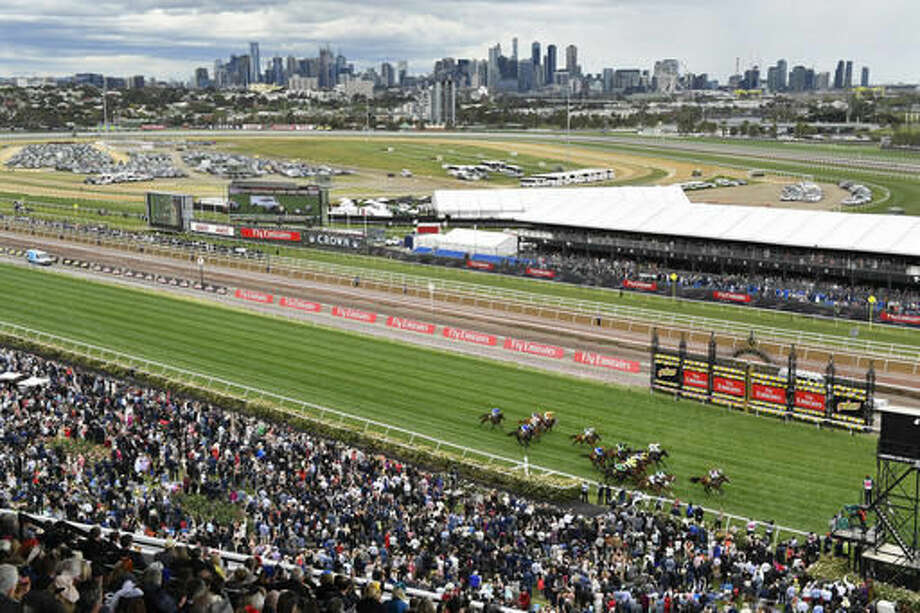 The city of Melbourne is seen as horses cross the finish line in race five before the running of the Melbourne Cup horse racing at the Flemington Racecourse in Melbourne, Australia, Tuesday, Nov. 1, 2016. (AP Photo/Andy Brownbill)