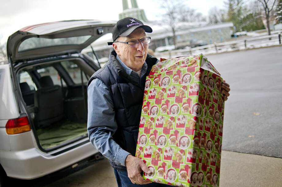 Volunteer Dennis Buckler carries a gift from Olimpia Vitale's vehicle during this year's United Way of Midland County Sharing Tree program gift distribution day on Monday at Blessed Sacrament Church. Photo: NICK KING | Nking@mdn.net