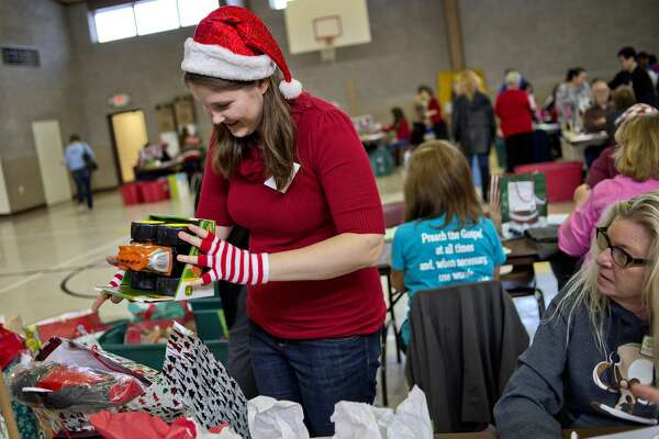 Volunteer Kathryn Getzinger sorts gift bags during this year's United Way of Midland County Sharing Tree program gift distribution day on Monday at Blessed Sacrament Church. Getzinger was working with a group from the West Midland Family Center.