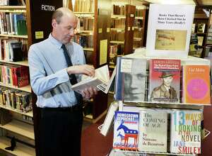 "Head of collection development Joe Nash with a display of ""books no one has checked out in years"" at the William K. Sanford Town Library Tuesday April 12, 2016 in Colonie, NY.  (John Carl D'Annibale / Times Union)"