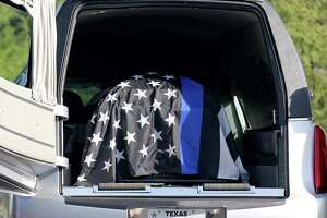 The flag draped casket of San Antonio Police Department Detective Benjamin Marconi, who was killed outside police headquarters last week, is seen in the hearse before being transferred to a horse-drawn carriage during the funeral held Monday Nov. 28, 2016 at Community Bible Church.