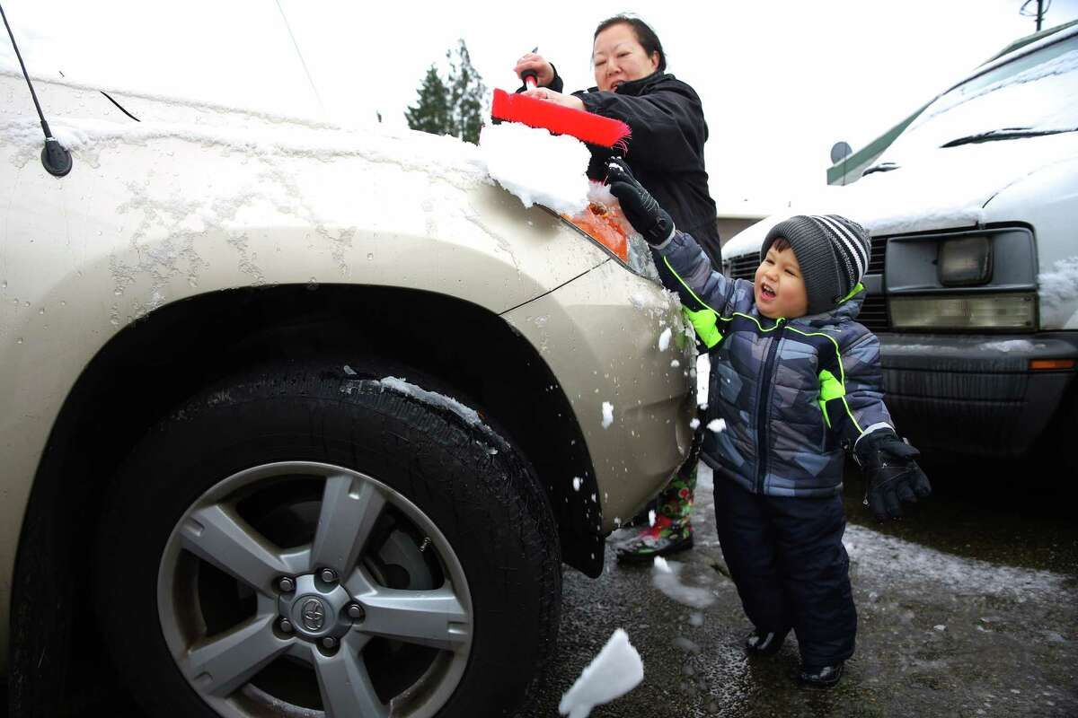 Two-year-old Malino Schlegel helps his grandmother Norma Schlegel brush the snow off her car in front of their house in south Rainier Beach, Monday, Dec. 5, 2016. Areas of King County over 400 feet saw some snow fall early Monday morning.