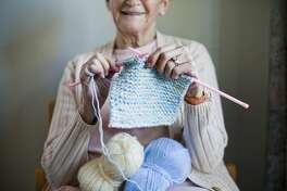Elderly woman knitting scarf