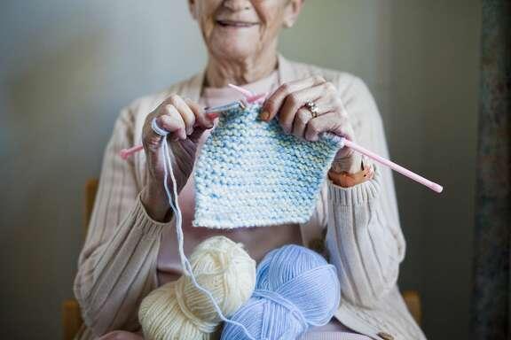 Elderly woman knitting scarf