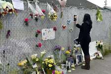 Janet Lino of Oakland touches a photograph of a victim at a memorial near the scene of the Ghost Ship artist warehouse fire in Oakland, CA, on Monday, December 5, 2016.