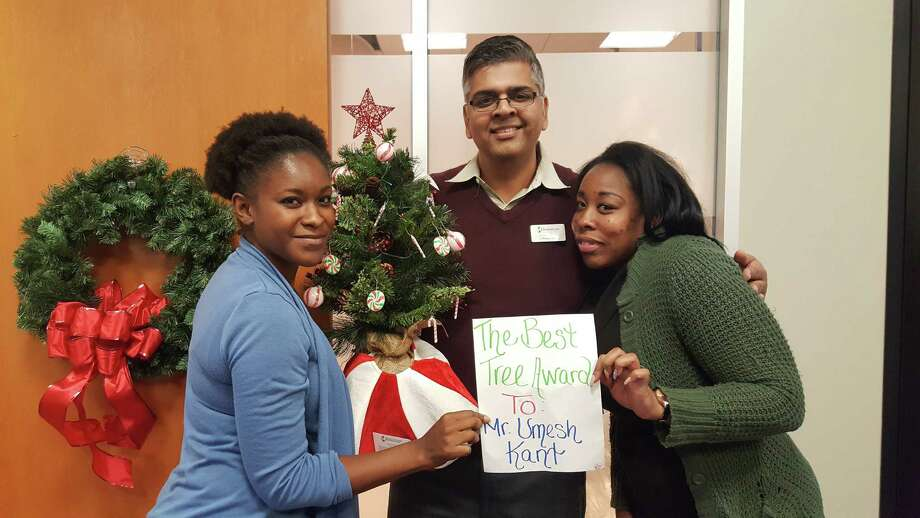 LaKendra Moutry (left), Umesh Kant (center) and Nicole Jenkins (right), from Oakmont Nursing and Rehabilitation Center in Humble, pose with the miniature tree they donated to Hope Forest during the Hope Forest Open House event at TriCare Hospice in Kingwood Dec. 1. Photo: Melanie Feuk