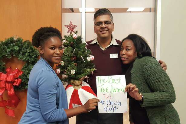 LaKendra Moutry (left), Umesh Kant (center) and Nicole Jenkins (right), from Oakmont Nursing and Rehabilitation Center in Humble, pose with the miniature tree they donated to Hope Forest during the Hope Forest Open House event at TriCare Hospice in Kingwood Dec. 1.