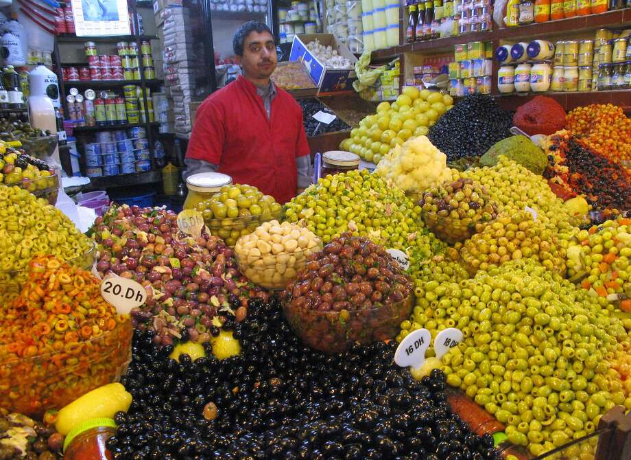 """""""In travel, all our senses are singed by the new. Added to the visual bombardment are masses of sounds, aromas, flavors, sensations...,"""" for example, a marketplace vendor in Tangier. Photo: Spud Hilton, The Chronicle"""