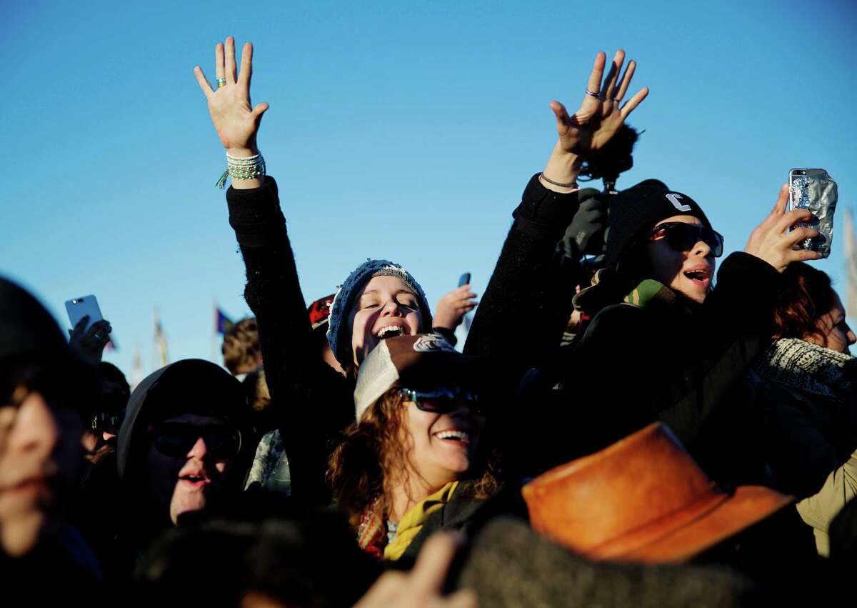 People celebrate at the Oceti Sakowin camp after it was announced that the U.S. Army Corps of Engineers won't grant easement for the Dakota Access oil pipeline in Cannon Ball, N.D., Sunday, Dec. 4, 2016. (AP Photo/David Goldman)