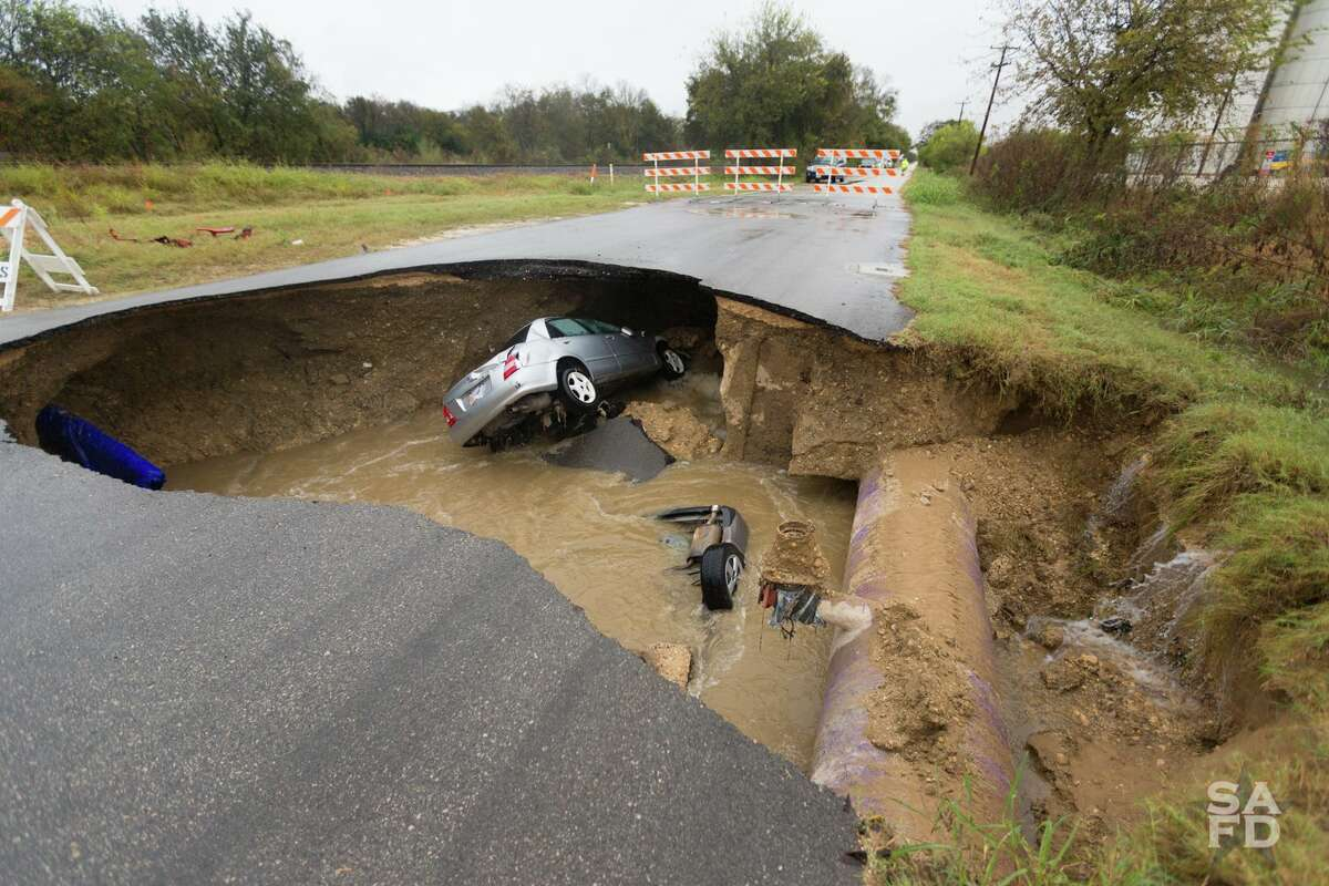 The San Antonio Fire Department worked to recover two vehicles from a large sinkhole that opened up Dec. 4, 2016 in the 8400 block of Quintana Road. Chief Charles Hood said the department has confirmed a body is inside one of the vehicles.