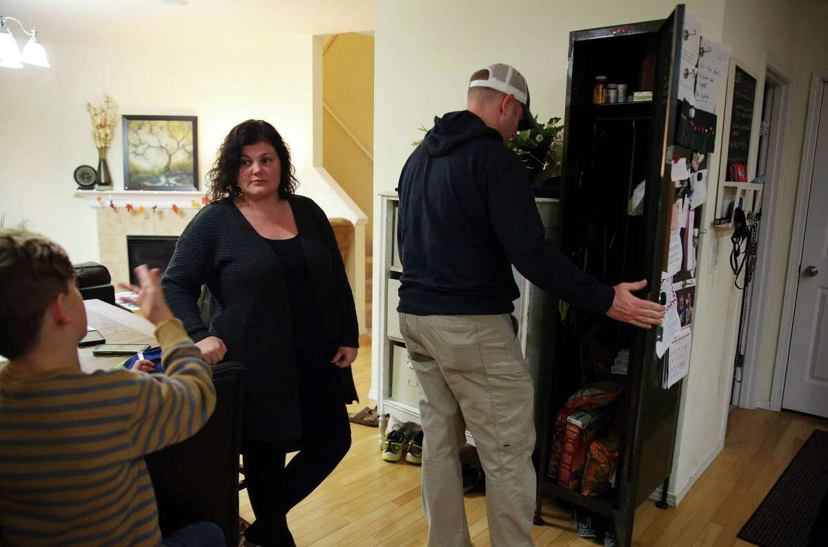 Mark McClanathan opens a locker in the family's kitchen where all potentially dangerous household items, including scissors, knives, medications and junk food, are kept under lock and key, as his wife Carmen speaks with their son, Nov. 17, 2016. Two years ago their 14-year-old daughter began showing signs of mental illness and suicidal tendencies. Almost overnight she was hospitalized, diagnosed with borderline personality disorder, and spent much of the following nine months at an adolescent psychiatric facility in Nevada. There are currently no long-term facilities for adolescents in Washington state. She has just recently been able to begin attending school again.