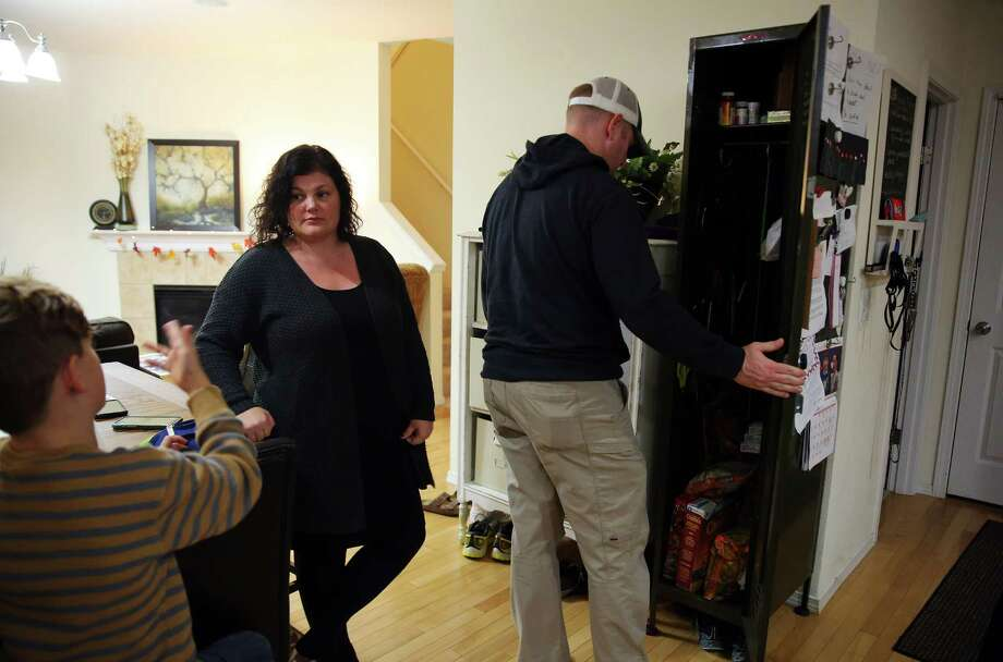 Mark McClanathan opens a locker in the family's kitchen where all potentially dangerous household items, including scissors, knives, medications and junk food, are kept under lock and key, as his wife Carmen speaks with their son, Nov. 17, 2016.  Two years ago their 14-year-old daughter began showing signs of mental illness and suicidal tendencies.  Almost overnight she was hospitalized, diagnosed with borderline personality disorder, and spent much of the following nine months at an adolescent psychiatric facility in Nevada. There are currently no long-term facilities for adolescents in Washington state.  She has just recently been able to begin attending school again. Photo: GENNA MARTIN, SEATTLEPI.COM / SEATTLEPI.COM