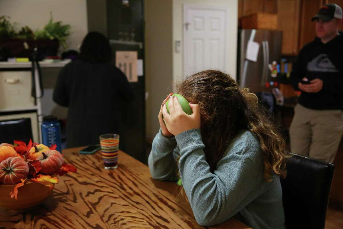 Sixteen-year-old B. drinks the milk out of her cereal bowl as her parents, Mark and Carmen McClanathan, talk in their kitchen, Nov. 17, 2016.