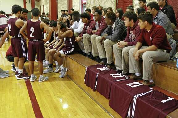Four jerseys from the St. Anthony's team were left on the bench to show which players were not able to play in St. Anthony's Alumni Tournament on Nov. 17, 2016.