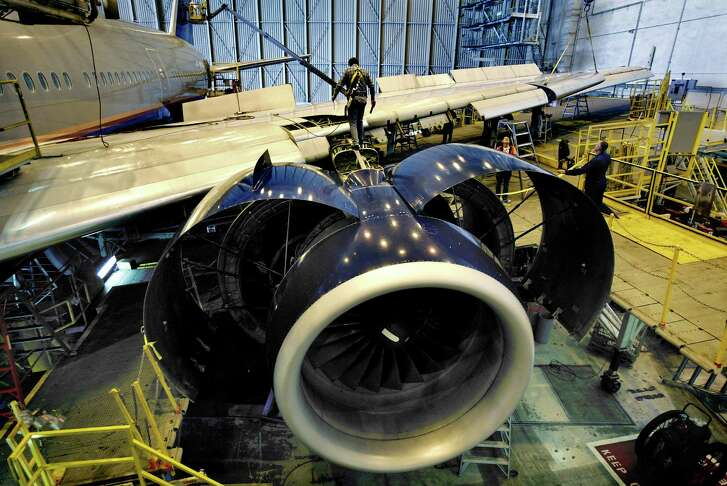 Technician Stan Odell walks near the engine of a United Boeing 777 inside a San Francisco hanger.
