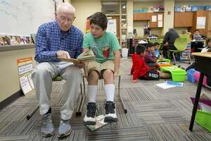 In this Thursday, Oct 13, 2016 photo, Dick Leeper, left, reads to Dominick Carroll at Roosevelt Elementary School in Council Bluffs, Iowa. The octogenarian has walked through the doors of Council Bluffs' Roosevelt Elementary almost every school day for 16 years. While his friends are enjoying retirement on the golf course, Leeper is ambling down the school hallways with a smile. (Kent Sievers/The World-Herald via AP)