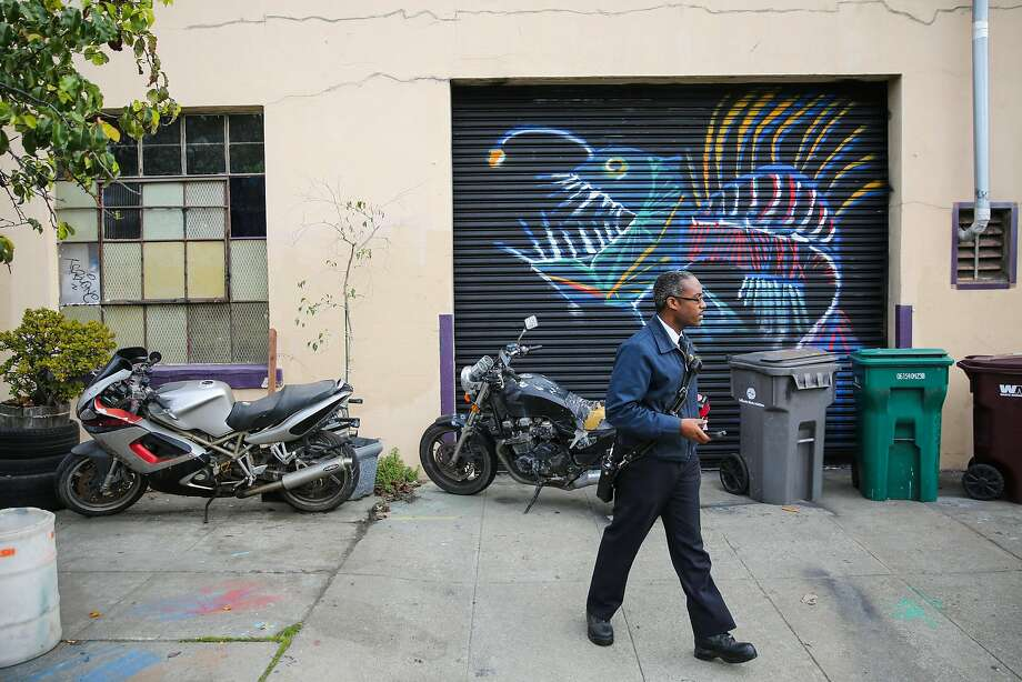 """An Oakland Fire inspector who declined to give his name walks around the perimeter of a warehouse known as Deathtrap in Oakland. The inspector was responding to a complaint. He said the city is trying to hold owners to """"a higher standard,"""" and to """"empower tenants, not displace them."""" Photo: Gabrielle Lurie, The Chronicle"""