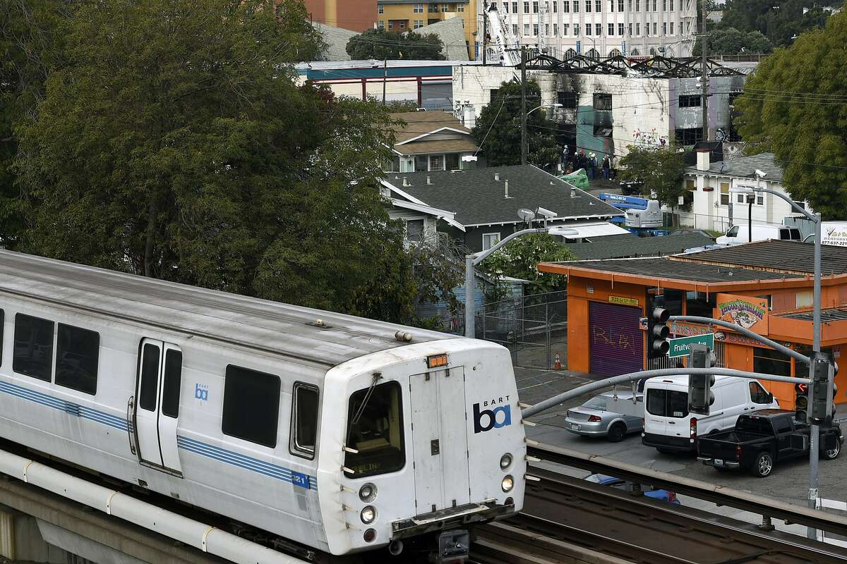 A BART train runs along the tracks with the burnt remains of the Ghost Ship artist warehouse in the background, in Oakland, CA, on Monday, December 5, 2016.
