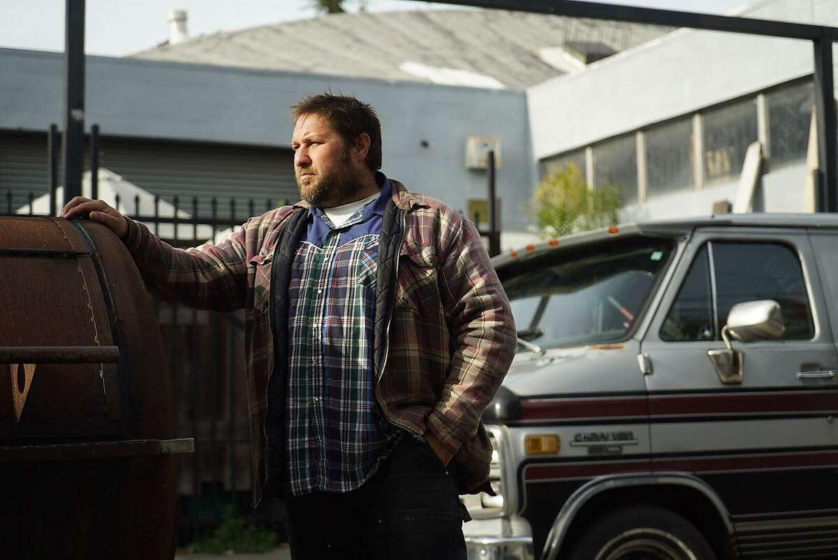 """Luke Woll poses for a photograph in front of his homemade grill called the """"Flavor Beast"""" that he used to cook at a recent party in West Oakland."""