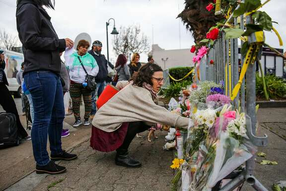 A woman places flowers at a memorial for fire victims near the Ghost Ship warehouse in Oakland, Calif., on Monday, December 5, 2016.