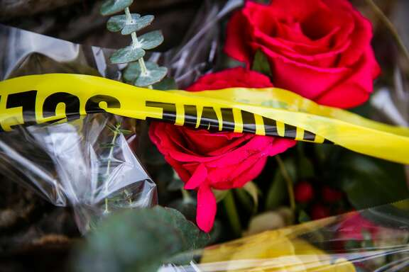 Roses are covered in crime scene tape are seen at a memorial for fire victims near the Ghost Ship warehouse in Oakland, Calif., on Monday, December 5, 2016.