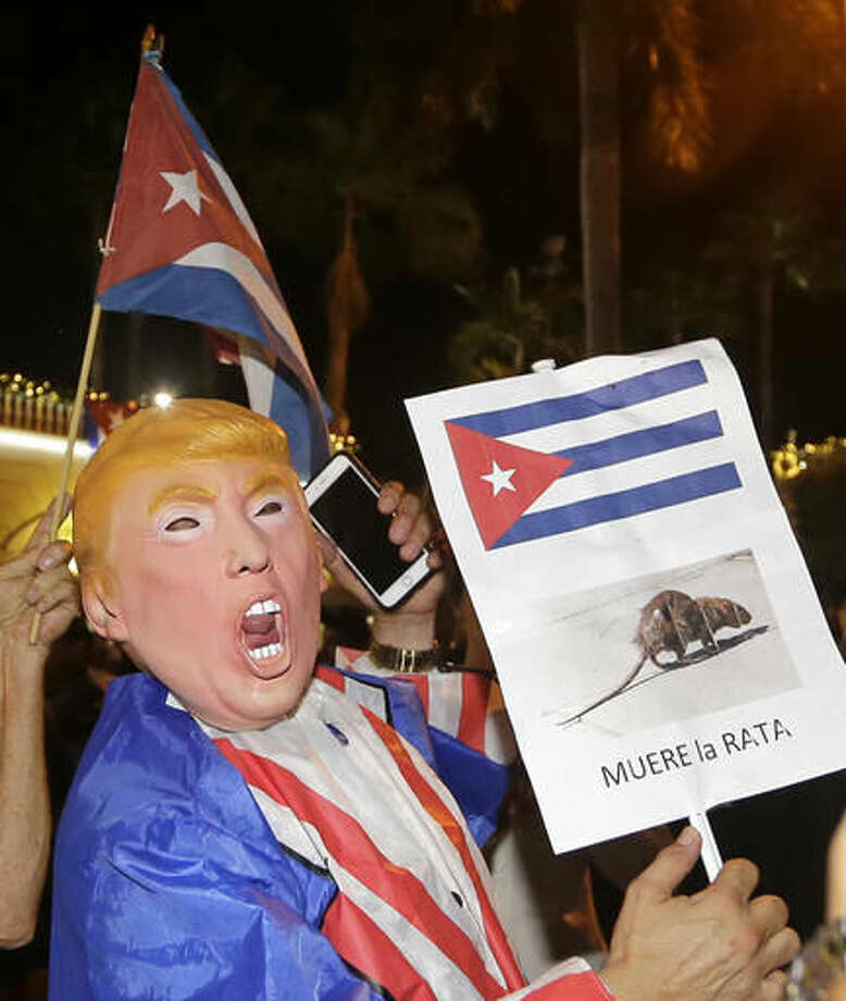 A person wearing a Donald Trump mask holds a sign in Spanish that reads the Rat Dies as he celebrates the death of Fidel Castro Saturday, Nov. 26, 2016, in the Little Havana area in Miami. Castro died eight years after ill health forced him to formally hand power over to his younger brother Raul, who announced his death late Friday, Nov. 25, on state television. (AP Photo/Alan Diaz) Photo: Alan Diaz