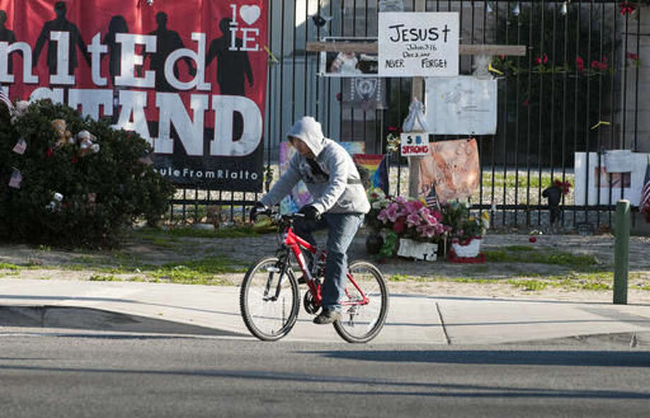 A cyclist passes memorial items displayed at the Inland Regional Center, the site of last year's terror attack, in San Bernardino, Calif., Thursday Dec. 1, 2016. Friday will mark the one year anniversary of the attack. (James Quigg/The Daily Press via AP) Photo: James Quigg