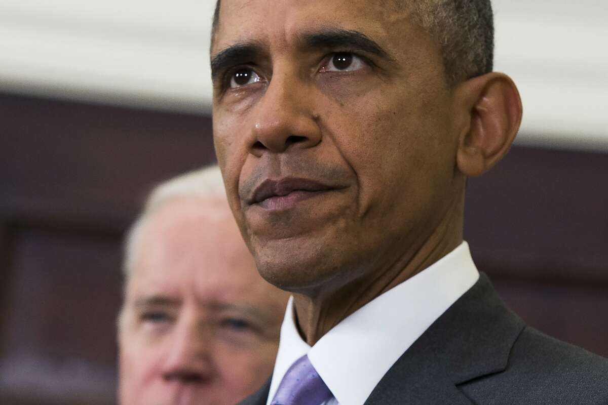 FILE - In this Feb. 11, 2015, file photo, Vice President Joe Biden listens at left, as President Barack Obama speaks about the Islamic State group in the Roosevelt Room of the White House in Washington. (AP Photo/Evan Vucci)
