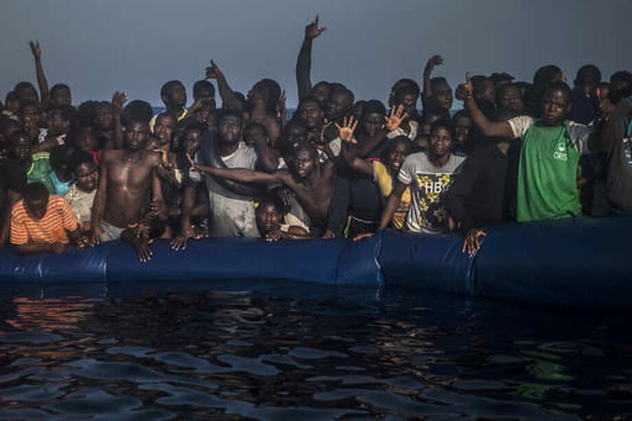 FILE- In this Saturday Sept. 10, 2016 file photo, African refugees and migrants react aboard a partially punctured rubber boat as they wait to be assisted , during a rescue operation on the Mediterranean Sea, about 13 miles North of Sabratha, Lybia. A popular Gambian wrestler has drowned trying to cross the Mediterranean Sea, the second high-profile athlete from the West African nation in the space of a few weeks to die trying to get to Europe on a boat of migrants. (AP Photo/Santi Palacios File) Photo: Santi Palacios