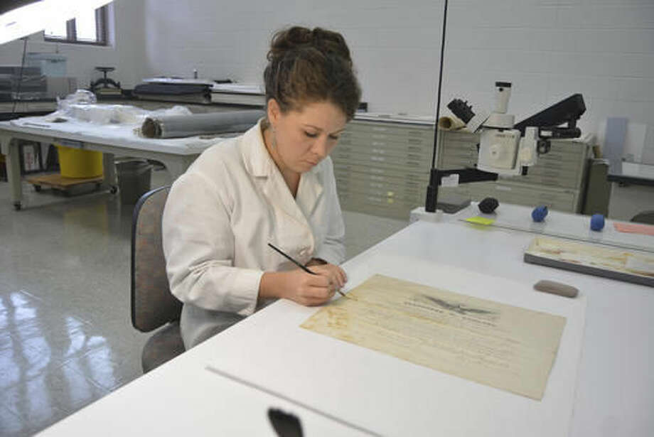 In this June 14, 2016 photo, Hilary Lefevere brushes away mold on a historical document at the Ford Conservation Center, in Omaha, Neb. The document appointed August Raasch the postmaster of Norfolk in 1868. (Dennis Meyer/The Norfolk Daily News via AP) Photo: Dennis Meyer