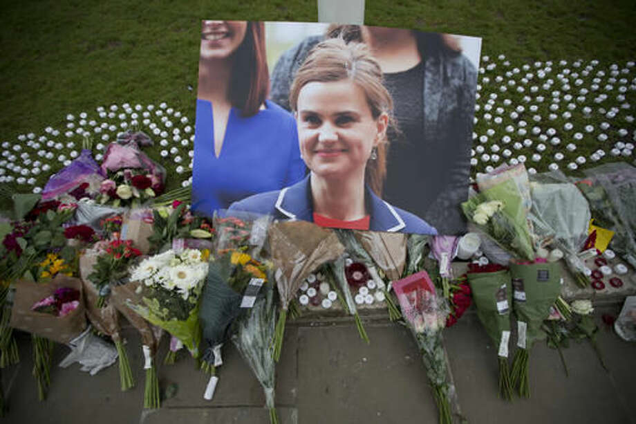 FILE - This is a Friday, June 17, 2016, file photo of an image and floral tributes for Jo Cox, in Parliament Square, outside the House of Parliament in London, after the 41-year-old British Member of Parliament was fatally injured in northern England. A jury Wednesday Nov. 23, 2016 found Thomas Mair with white supremacist views guilty of murdering Labour lawmaker Jo Cox a week before Britain's EU membership referendum. (AP Photo/Matt Dunham, File) Photo: Matt Dunham