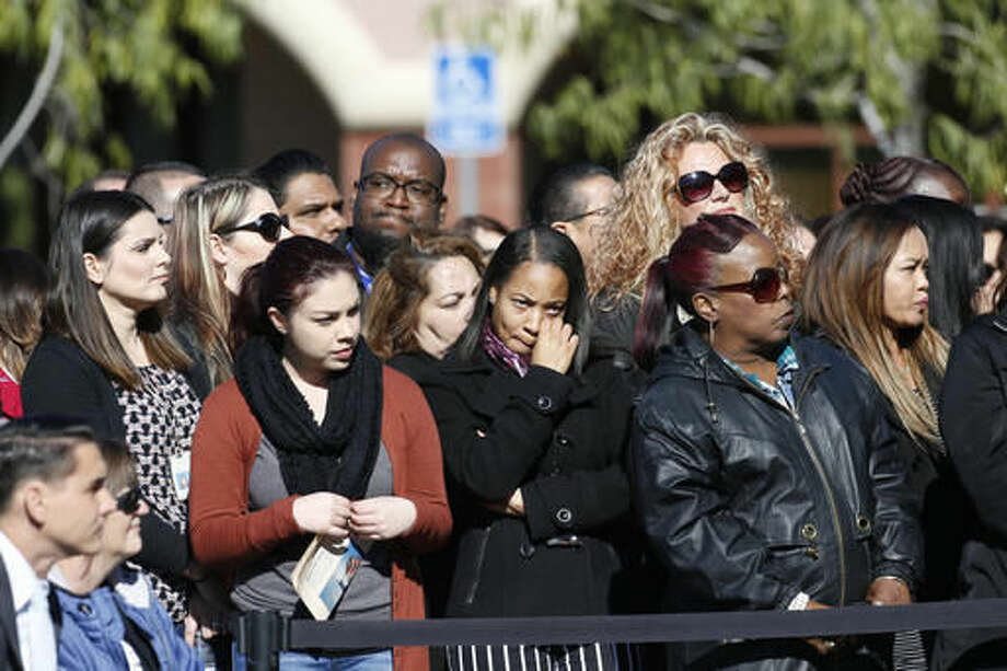 A crowd watches during a moment of silence for county workers at the Inland Regional Center in San Bernardino, Calif., Friday, Dec. 2, 2016. At the moment when shooters unleashed terror on San Bernardino a year ago, county employees remembered their fallen colleagues with a moment of silence late Friday morning. (AP Photo/Nick Ut) Photo: Nick Ut