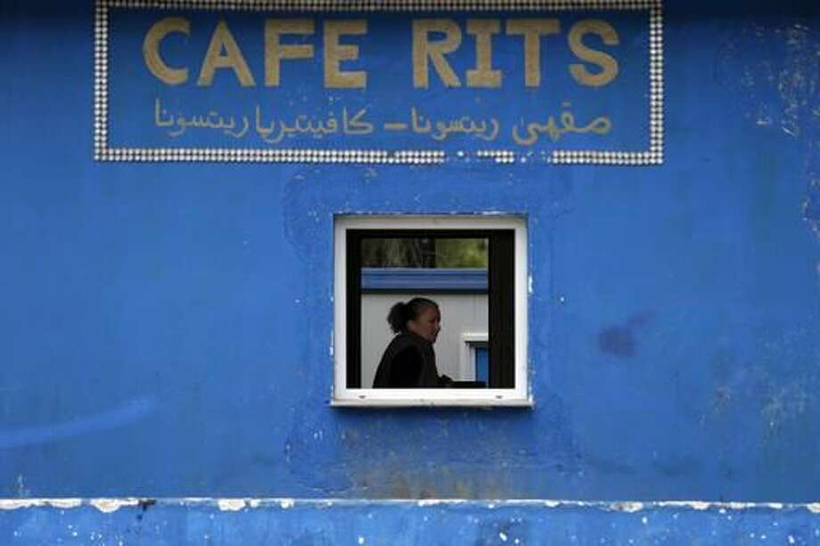 A woman works inside a cafe at the refugee camp of Ritsona about 86 kilometers (53 miles) north of Athens, on Tuesday, Nov. 22, 2016. Around 680 people are staying in new container houses as over 62,000 refugees and migrants are stranded in Greece after a series of Balkan border closures. (AP Photo/Thanassis Stavrakis) Photo: Thanassis Stavrakis