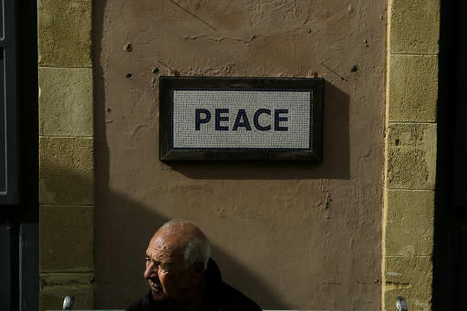 """An elderly Cypriot man sits on a bench with a sign reading """"Peace"""" near a main checkpoint in Ledras street in divided capital Nicosia in this eastern Mediterranean island of Cyprus, on Friday, Dec. 2, 2016. Greek Cypriot President Nicos Anastasiades and breakaway Turkish Cypriot leader Mustafa Akinci agreed to meet in Geneva next month in a four-day summit to decide on the key issues of territory and post-settlement security arrangements. (AP Photo/Petros Karadjias) Photo: Petros Karadjias"""