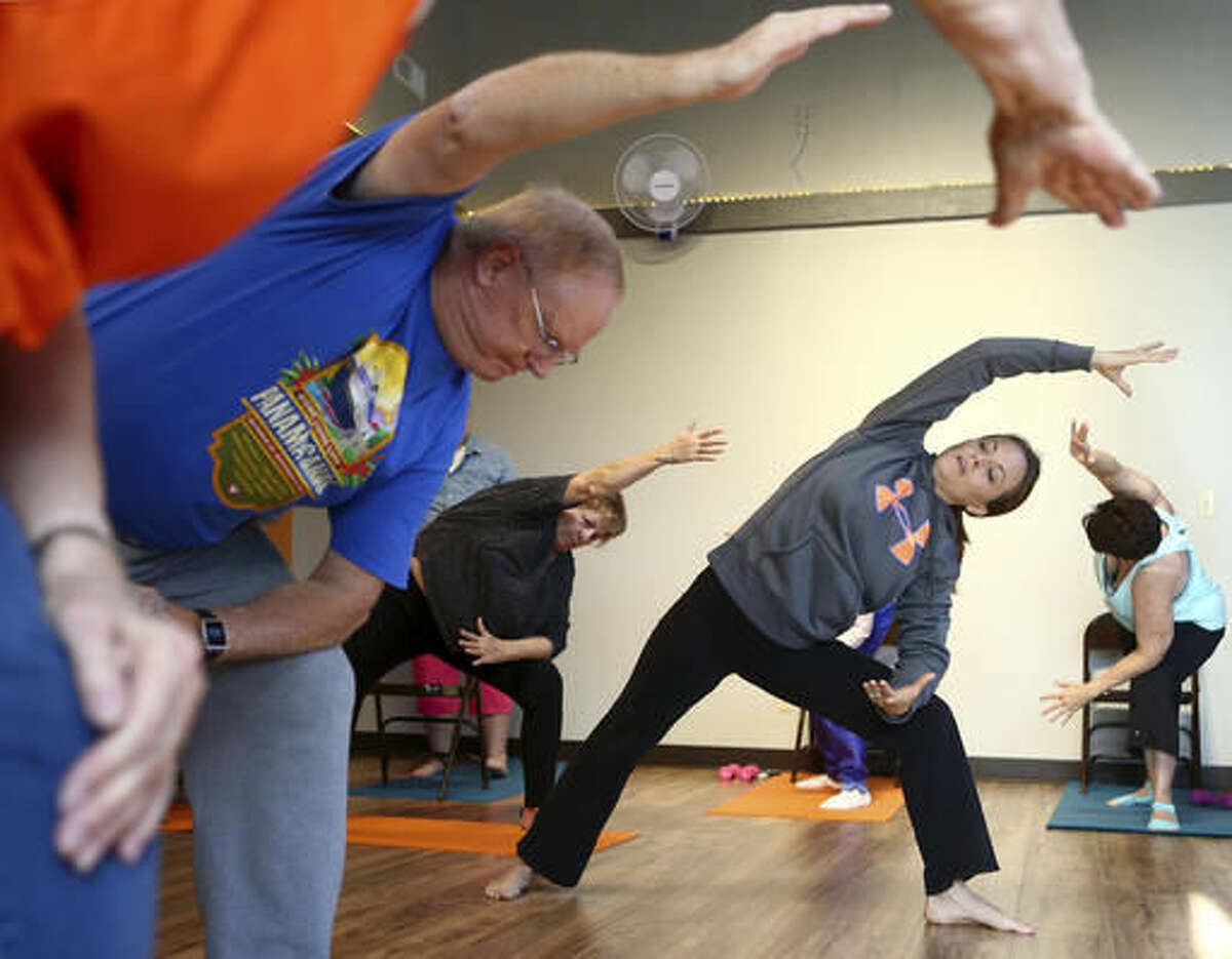 In this Nov. 18, 2016 photo, Tina Miser, right, leads a chair yoga class at Joyful Yoga in Peru, Ind. (AP Photo/Kokomo Tribune, Kelly Lafferty)