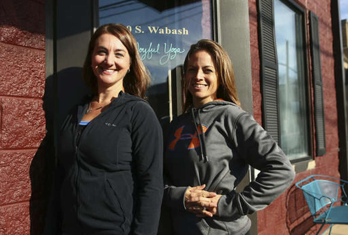 In this Nov. 18, 2016 photo, Joyful Yoga owners Carrie Gallahan, left, and Tina Miser pose outside their studio in Peru, Ind. The two opened the place in December of 2015 which boasts a comfortable workout space with a wooden floor and a skylight that floods the studio with sunlight. (Kelly Lafferty Gerber/Kokomo Tribune via AP)