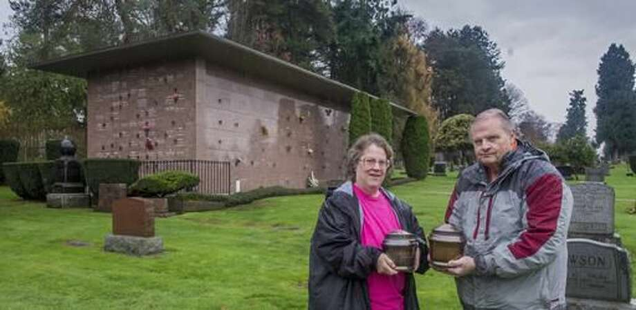 In this Nov. 16, 2016 photo, Loretta and Jim Dimond hold metal urns containing the ashes of Civil War veteran James Powers and his wife Irena Powers in Lake View Cemetery in Seattle, Wash. The urns sat unclaimed for decades in the mausoleum (rear) until discovered through a records search by Loretta Dimond of Kent. Her husband Jim Dimond and Bob Patrick of Missing in America Project gathered evidence and won the right for the remains to be intered at Tahoma National Cemtery in Kent in a ceremony in December. (Peter Haley/The News Tribune via AP) Photo: Peter Haley