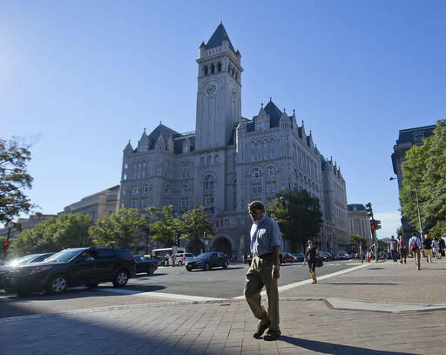 FILE - In this Monday, Sept. 12, 2016, file photo, pedestrians cross Pennsylvania Avenue across the street from the Trump International Hotel in downtown Washington. Several experts in government contract law say that President-elect Donald Trump will have to give up his stake in his prized Washington, D.C. hotel if he wants to be president. (AP Photo/Pablo Martinez Monsivais, File) Photo: Pablo Martinez Monsivais