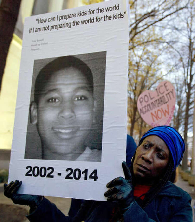 FILE - In this Dec. 1, 2014 file photo, Tomiko Shine holds up a picture of Tamir Rice, the 12 year old boy fatally shot by a rookie police officer in Cleveland, Ohio, on Nov. 22, during a protest in Washington, D.C. Twelve-year-old Tamir Rice was fatally shot by a Cleveland police officer near a gazebo in a recreational area in November 2014. Officers were responding to a report of a man waving a gun. The boy, who had a pellet gun tucked in his waistband, was shot right after their cruiser skidded to a stop a few feet away. A grand jury in December 2015 declined to indict patrolman Timothy Loehmann, who fired the fatal shot, and training officer Frank Garmback. The city in 2016 agreed to settle a federal lawsuit filed by Tamir Rice's family for $6 million. (AP Photo/Jose Luis Magana, File) Photo: Jose Luis Magana