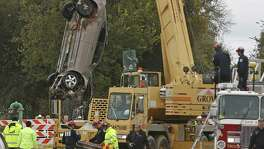 First car is taken out of the sinkhole at massive sinkhole on 8400 Quintana Road on Monday, December 5, 2016. A victim was still in this car when it was taken out of the sinkhole.