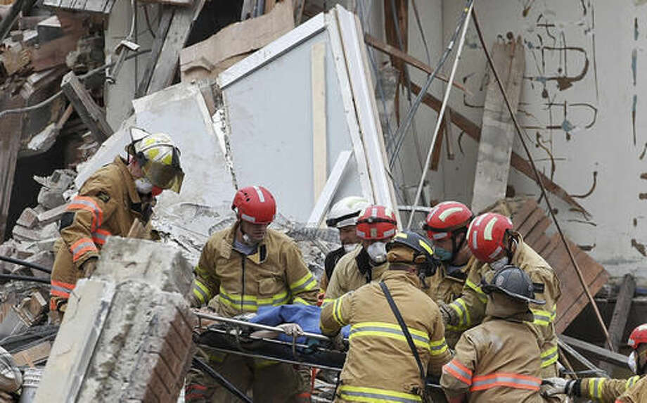 Emergency crews rescue a woman from a building collapse Friday Dec. 2, 2016 in downtown Sioux Falls. Two people were trapped inside the building, which was undergoing construction at the time of the collapse. A fire official says rescue workers are concerned about debris shifting as they try to free the people. (Joe Ahlquist/Argus Leader via AP) Photo: Joe Ahlquist