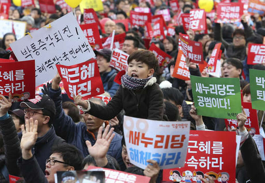 """Protesters shout slogans as they march toward the presidential house during a rally calling for South Korean President Park Geun-hye to step down in Seoul, South Korea, Saturday, Dec. 3, 2016. Hundreds of thousands of South Koreans marched in the capital for the sixth straight Saturday calling for the removal of scandal-plagued Park, who faces an impeachment vote in parliament next week. The banners read: """"Park Geun-hye to step down."""" (AP Photo/Ahn Young-joon). Photo: Ahn Young-joon"""