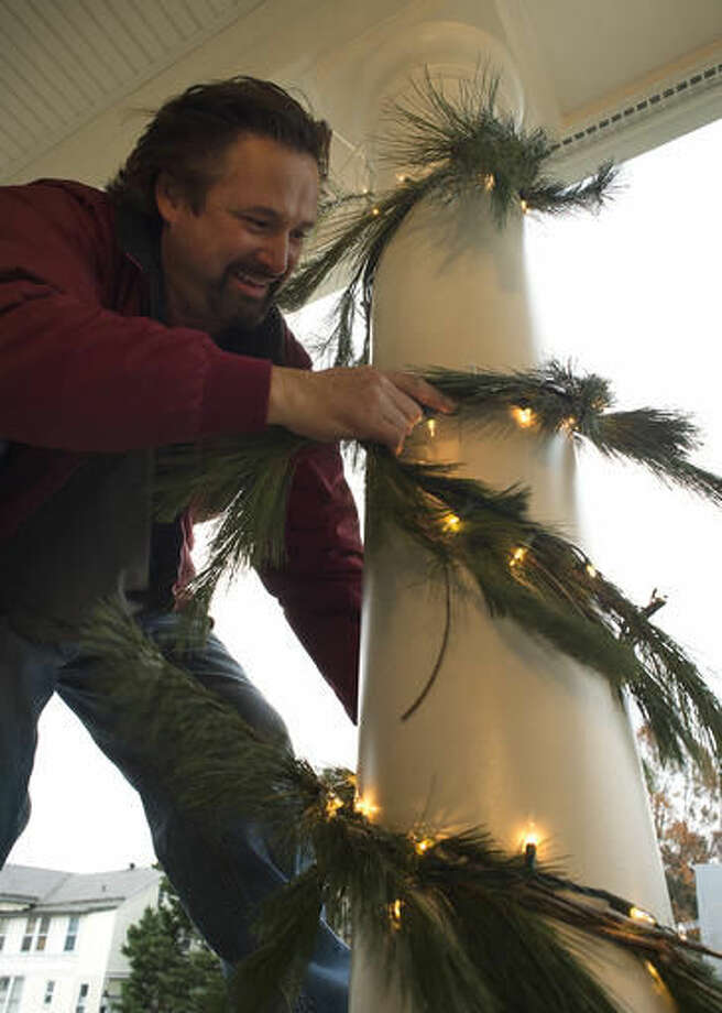 ADVANCE FOR WEEKEND EDITIONS, DEC. 3-4 - In this Nov. 23, 2016 photo, Ron Layman, owner of The King of Christmas, wraps garland and lights on the column of a house in Frederick, Md. (Dan Gross/The Frederick News-Post via AP) Photo: Dan Gross
