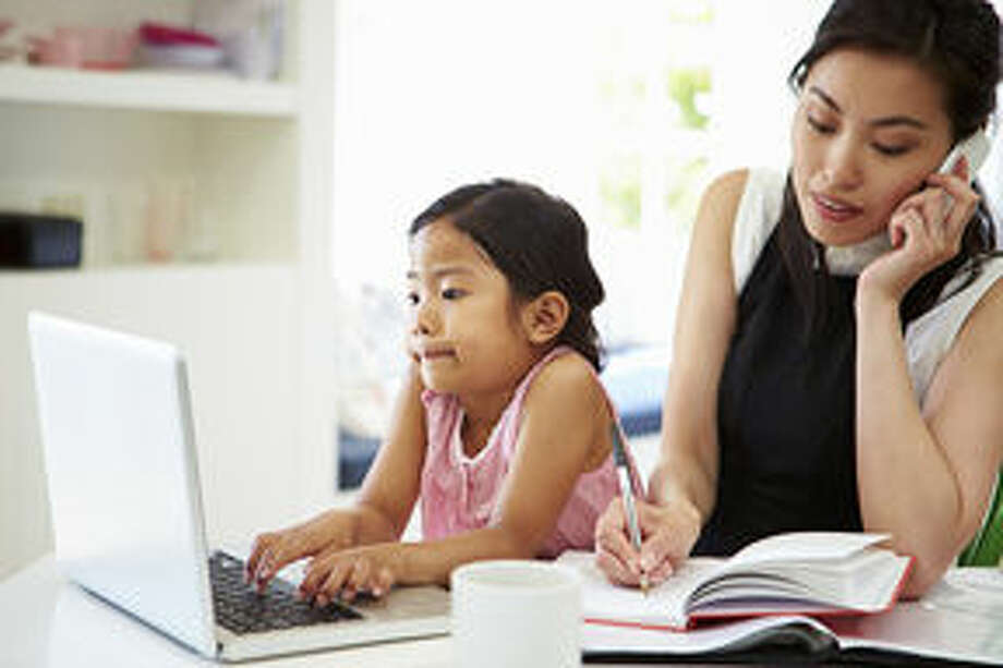 Busy Mother Working From Home With Daughter Photo: Monkey Business Images