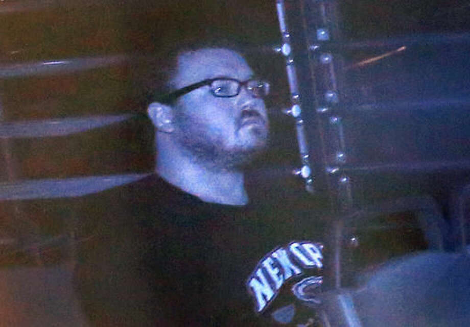 FILE - In this Monday, Nov. 10. 2014, file photo taken through tinted glass, Rurik Jutting, a British banker, is escorted in a prison bus to a court in Hong Kong. Rurik was convicted of murder Tuesday for killing two Indonesian women in Hong Kong, torturing one of them over three days while using cocaine in a gruesome case that shocked the Chinese financial hub. (AP Photo/Vincent Yu, File) Photo: Vincent Yu