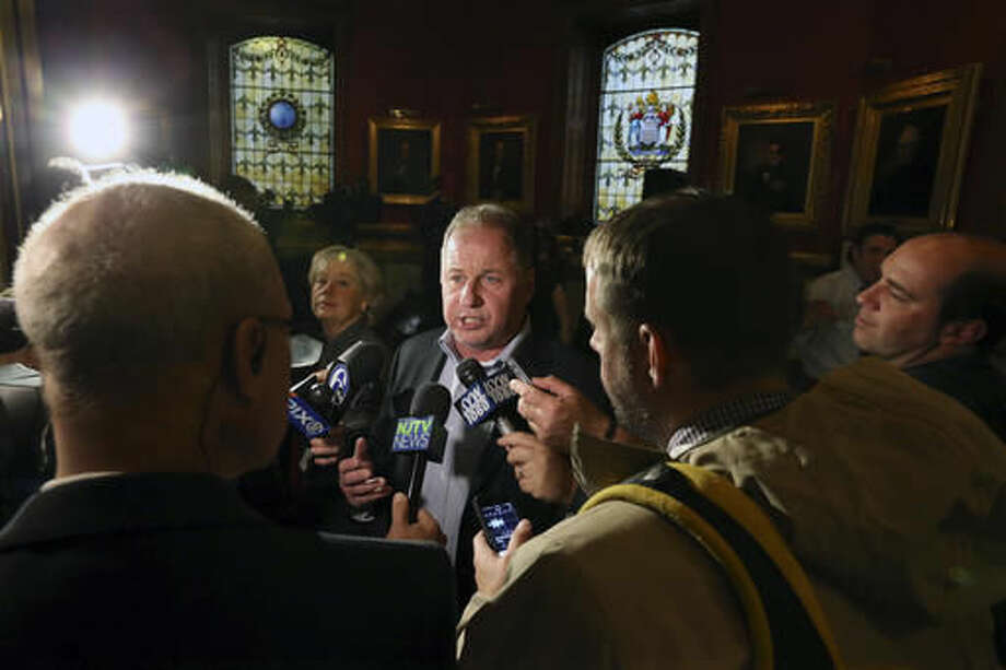 William Brennan, a former Teaneck, N.J., a firefighter, answers a question in the Statehouse rotunda after New Jersey Gov. Chris Christie addressed a gathering in the rotunda, telling them that work will begin immediately on a complete renovation of the statehouse, Tuesday, Nov. 29, 2016, in Trenton, N.J. Brennan discussed his citizen's complaint that Christie failed to put a stop to the closure of lanes at the George Washington Bridge in 2013. On Wednesday, Christie faces a court date in Superior Court over the citizen's complaint that he committed official misconduct by not reopening the lanes when he found out about their closure. (AP Photo/Mel Evans) Photo: Mel Evans