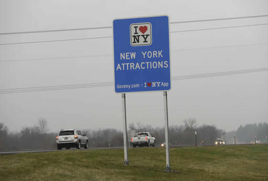 """Vehicles pass an """"I Love New York"""" sign on the New York State Thruway, Tuesday, Nov. 29, 2016, in Utica, N.Y. Officials with the Federal Highway Administration and the New York Department of Transportation will meet in December to discuss the removal of more than 500 """"I Love NY"""" signs from the state's roadways. FHA officials say the signs don't conform to federal standards and pose a dangerous distraction for motorists. (AP Photo/Mike Groll) Photo: Mike Groll"""