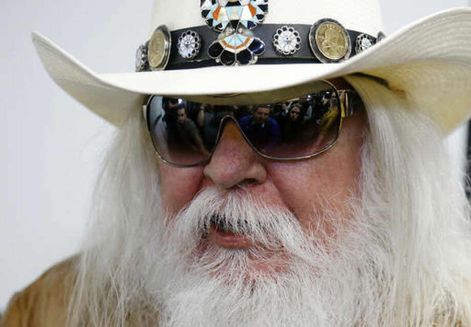 FILE - In this Jan. 29, 2013, file photo, reporters are reflected in the sunglasses of Leon Russell as he answers a question at a news conference in Tulsa, Okla. Russell, who sang, wrote and produced some of rock 'n' roll's top records, has died. (AP Photo/Sue Ogrocki, File) Photo: Sue Ogrocki