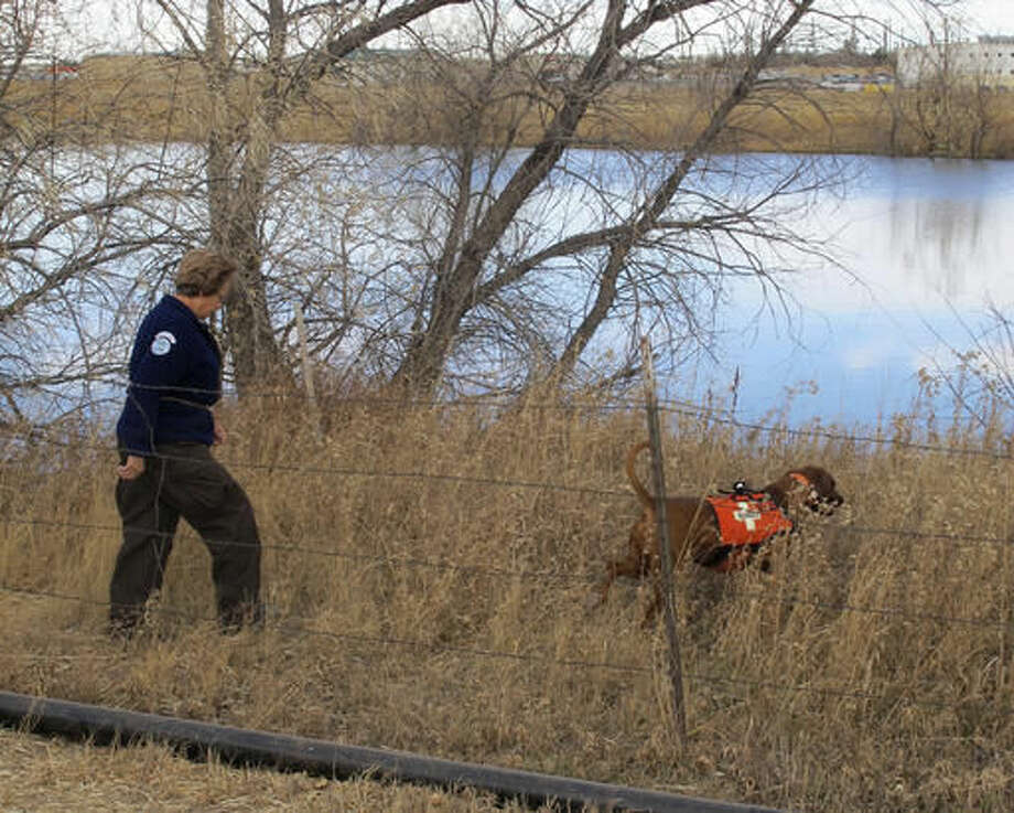 Laramie County Sheriff's Office deputy Mel Gothard follows a search dog named Copper around a lake on the outskirts of Cheyenne, Wyo., Wednesday, Nov. 16, 2016. Divers searched the lake unsuccessfully for the remains of 13-month old Silas Ojeda, who's been missing since late October. Authorities earlier searched a landfill in Northern Colorado for the boy's remains. (AP Photo/Ben Neary) Photo: Ben Neary